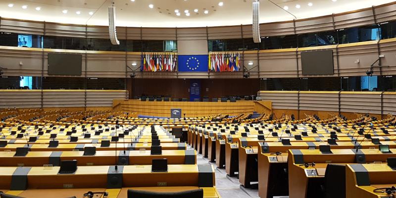 Immagine di una sala conferenze vuota con uno schermo che mostra la bandiera europea