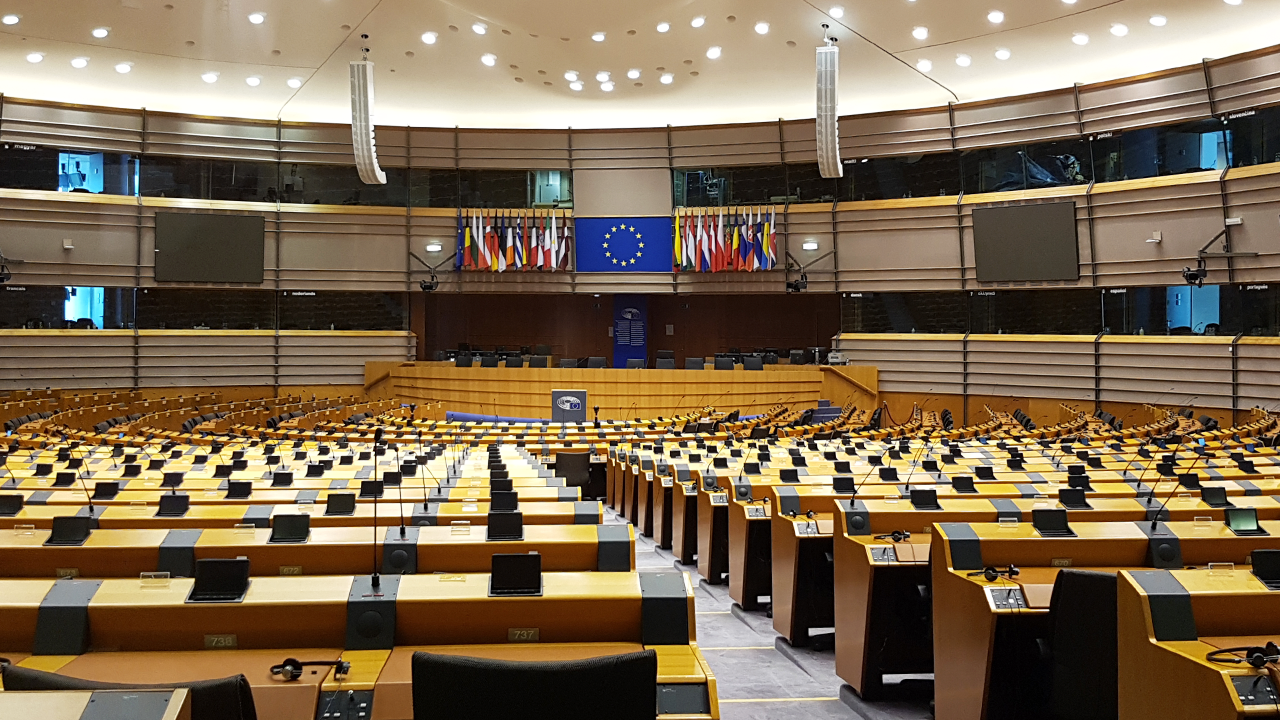 Image of an empty conference room with a large screen and the European flag on it